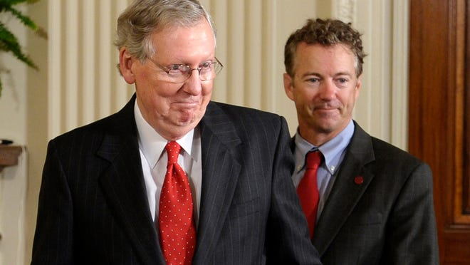 Sens. Mitch McConnell, left, and Rand Paul arrive in the East Room of the White House on July 23, 2013, for a ceremony where President Obama honored the 2013 NCAA champion Louisville Cardinals.
