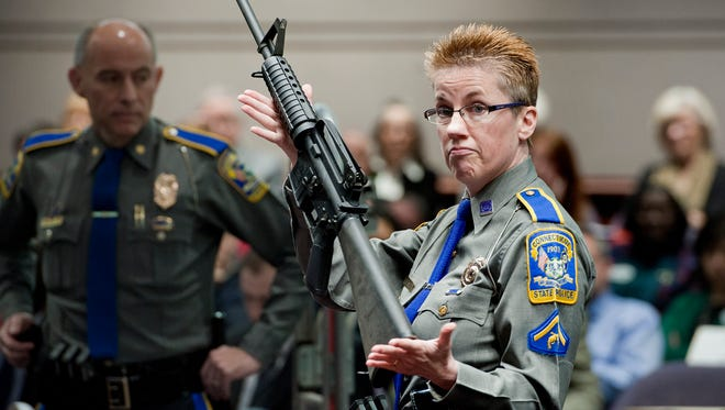 Detective Barbara J. Mattson, of the Connecticut State Police, holds up a Bushmaster AR-15 rifle, the same make and model of gun used by Adam Lanza in the Sandy Hook School shooting, for a demonstration during a hearing of a legislative subcommittee reviewing gun laws, at the Legislative Office Building in Hartford, Conn. The families of nine of the 26 people killed and a teacher injured on Dec. 14, 2012, at the Sandy Hook Elementary School filed a lawsuit against the manufacturer, distributor and seller of the Bushmaster AR-15 rifle used by Lanza in the shooting. (AP Photo/Jessica Hill, File) ORG XMIT: BX101