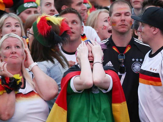 In this July 7, 2016 photo football supporters react to the first goal by France, at a public viewing of the Euro 2016 semi-final between France and Germany which was shown publicly  at Heiligengeistfeld in Hamburg, Germany. Germany lost 0-2. (Bodo Marks/dpa via AP)