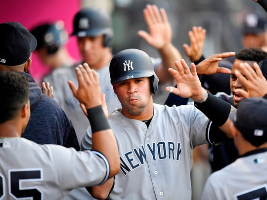 New York Yankees' Gary Sanchez is congratulated in the dugout after scoring on a triple by Aaron Hicks during the second inning against the Los Angeles Angels, Saturday, April 28, 2018, in Anaheim, Calif.