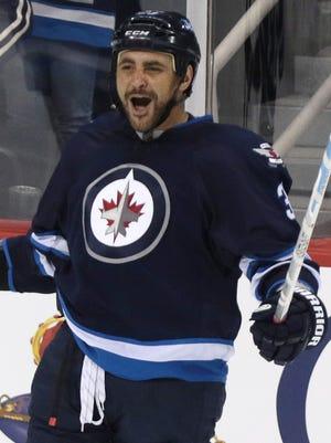 Winnipeg Jets defenseman Dustin Byfuglien celebrates after scoring in his first game back from injury.