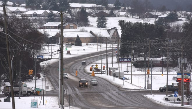Sparse, late-morning traffic makes its way down Frazeysburg Road near the intersection with Northpointe Drive on Monday.