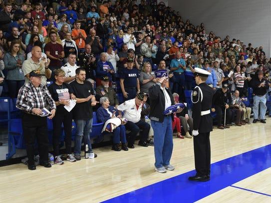 Korean War veteran Richard Scholz (with flag) returns