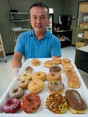 Noah Bounyalith, owner of Donuts D-Lite, displays some