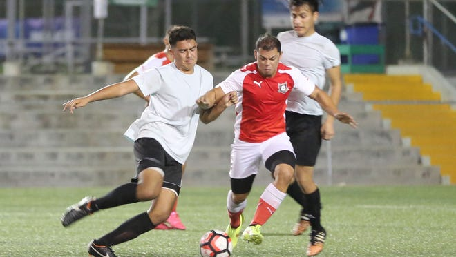 Islanders FC's Cameron Miles and Strykers DI's Caleb Barretto battle for possession of the ball during a Round 1 match of the Bank of Guam 9th Annual GFA Cup tournament main draw at the Guam Football Association National Training Center. Strykers DI won 9-1.