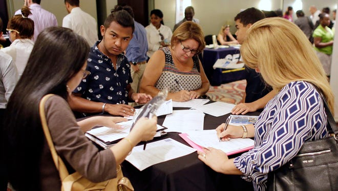 People fill out job applications at a job fair in Miami Lakes, Fla.