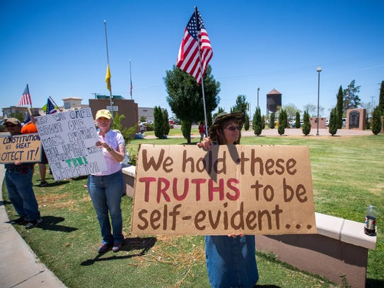 Diane Alfaro, center, holds a sign at the Stand By