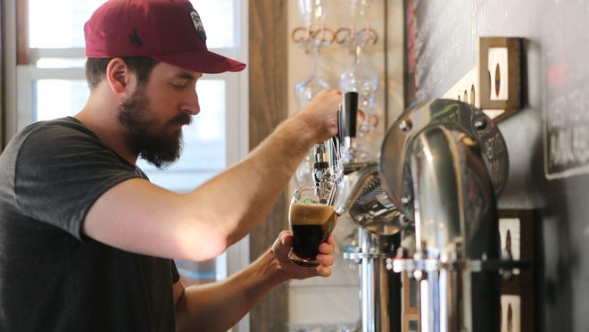Bartender Scott Ruel draws a beer from the tap at Seven Lakes Station in Sloatsburg.