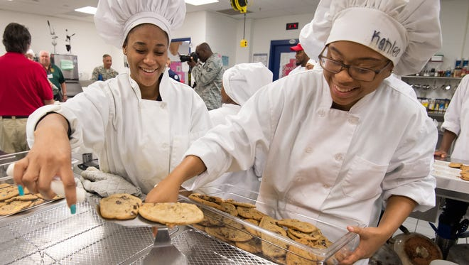 Baneighja Handy, left, and Kahlea Henry, sophomores at Middletown High School, place freshly baked cookies into a tray.  The cookies, donated by Bob Evans, will be sent to troops stationed overseas in partnership with the American Legion Auxiliary in Middletown.