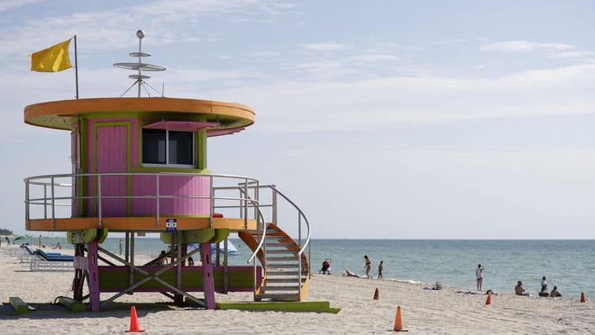 Beachgoers enjoy a day on the sand near a lifeguard stand, Wednesday, June 10, 2020, on Miami Beach, Florida's famed South Beach. Beaches in Miami-Dade County opened with restrictions Wednesday after having been closed for 12 weeks due to the COVID-19 outbreak.