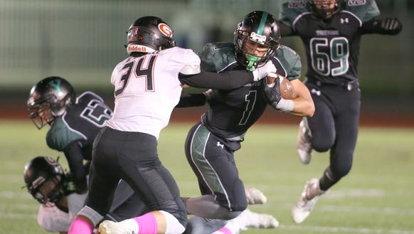 Yorktown's Brett Maker (1) fends off a tackler during