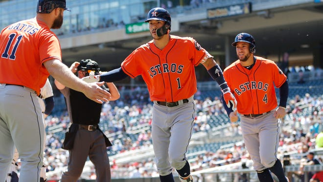 Houston Astros' Evan Gattis, left, congratulates Carlos Correa as he and George Springer, right, score on Correa's two-run home run off Minnesota Twins pitcher Hector Santiago in the first inning of a baseball game Wednesday, May 31, 2017 in Minneapolis.
