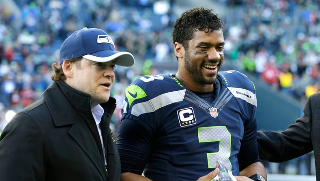 Seahawks GM John Schneider, left, will be looking to extend QB Russell Wilson's contract, which expires after the 2015 season.