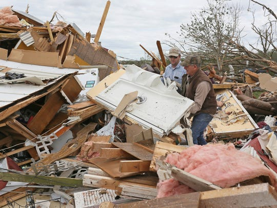 Roman Brown, left, and Sam Crawford, right, move part of a shower wall out of their way as they help a friend look for medicine in a destroyed home outside of Hamilton, Miss., after an apparent tornado touched down.