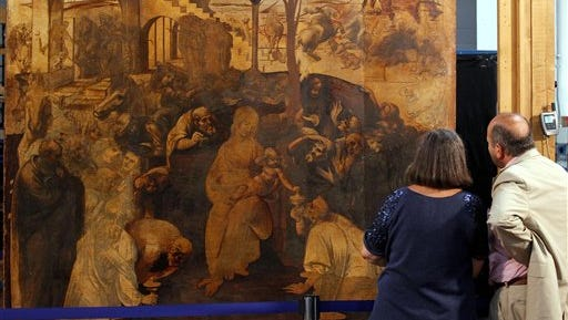"""People look at one of Leonardo da Vinci's most famous works, """"Adoration of the Magi,"""" during a press conference in Florence, Italy, Tuesday. Officials on Tuesday released findings of the first phase of the restoration, which is scheduled to be completed in 2015. They said the initial removal of grime showed new details and color in the work and gave insight into Leonardo's techniques, but also made clear that other artists were involved."""