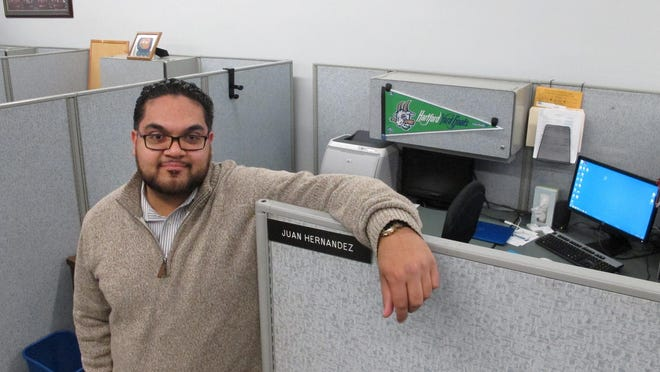 Juan Hernandez, an aide to a City Council member, poses at his work cubicle at City Hall in Hartford, Conn. Hernandez, 25, is among millennials nationwide with student debt who are worried about being able to qualify for a loan and come up with a down payment for a home.
