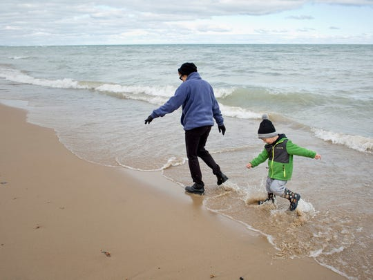 Matthew Kreiner, 3, stomps in the water in his rain boots while walking with his grandmother Pat Kreiner, of Port Huron Township, Wednesday, October 14, 2015 at Lakeside Park in Port Huron. A new restroom and concessions facility and splash pad will be constructed and open by May of 2016 as part of improvements at the park.