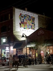 A sign for Brooklyn Outdoor hangs on a building in Eastern Market in Detroit.