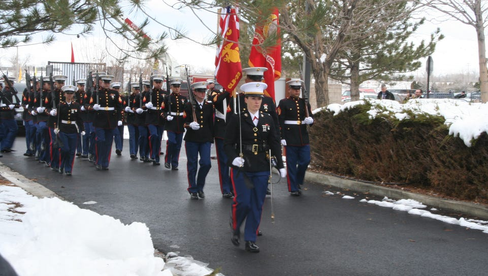 A Marine Corps color guard leads a procession at the