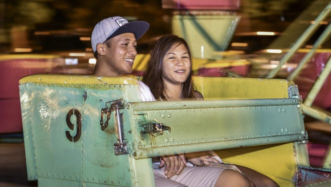 Gavin Salas of Agana Heights and Camilla Quenga of Barrigada ride the Scrambler at the Liberation Carnival in Tiyan on June 13.