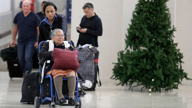 An employee pushes a woman on a wheelchair out of the international arrivals area on Terminal B at Newark Liberty International Airport on Nov. 21, 2017, in Newark, N.J.