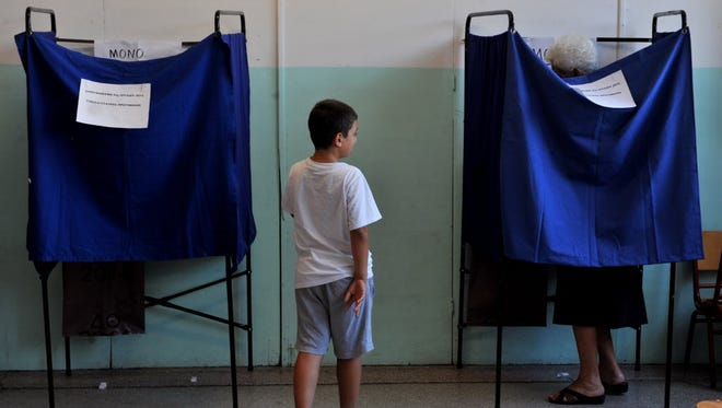 A young boy waits as his grandmother prepares her vote in a voting booth during the Greek referendum in Thessaloniki on July 5, 2015.