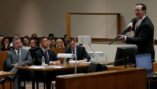 ADA William Gargan holds the weapon used to kill Liang Tan during closing arguments on Tuesday.