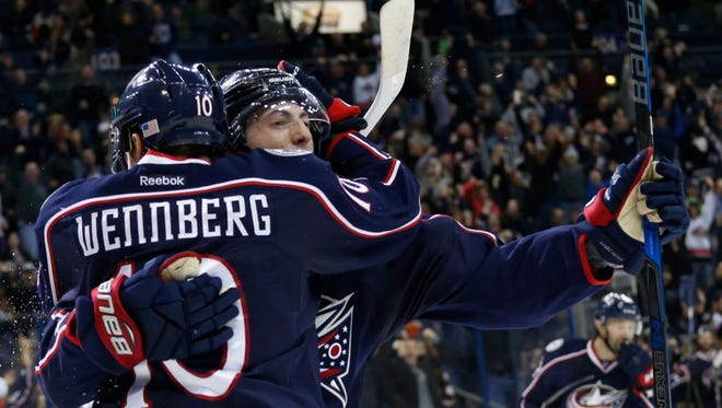 Zach Werenski, right, celebrates his game-winning goal against the Ducks with teammate Alexander Wennberg.