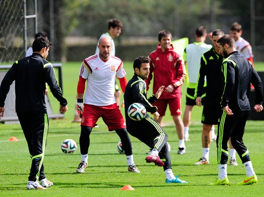 Spain's Cesc Fabregas, center, controls the ball during an official training session the day before the group B World Cup soccer match between Spain and Australia at the Atletico Paranaense training center in Curitiba, Brazil, Sunday, June 22, 2014. Spain will play in group B of the Brazil 2014 World Cup. (AP Photo/Manu Fernandez)
