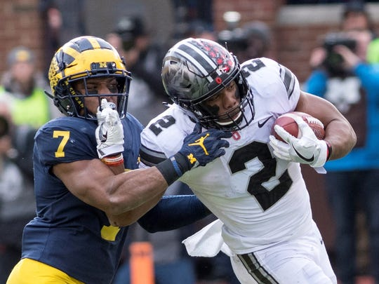 Ohio State freshman tailback J.K. Dobbins tries to stiff arm a Michigan defender in the Buckeyes' 31-20 victory.