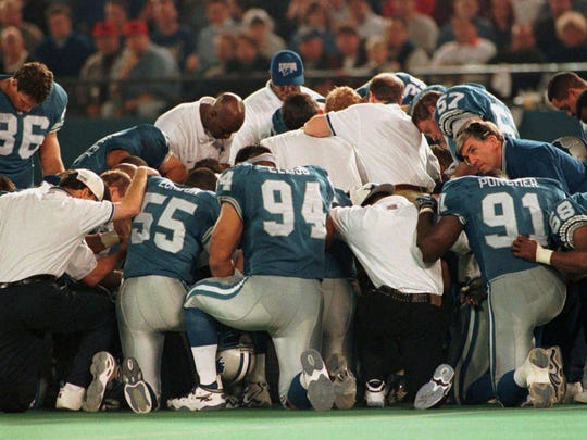 Detroit Lions players and staff pray on the field after