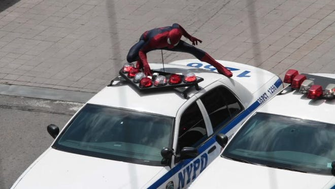 Spider-Man rides on top of a New York City police car on Main Street heading west in downtown Rochester on May 9.