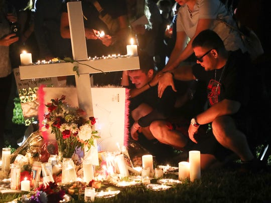 A day after a mass shooting at Marjory Stoneman Douglas High School on Feb. 14, 2018, mourners attend a candlelight vigil for those slain and injured. Thousands showed up for the vigil at the Parkland amphitheater.