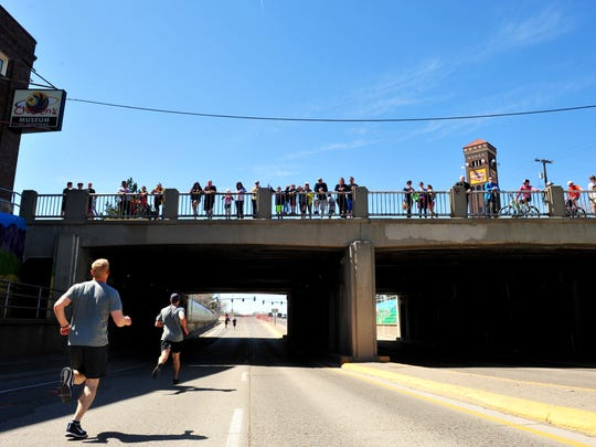 Spectators watch the 3-mile run from the train overpass at 1st Avenue North during the 39th Annual Ice Breaker Road Race last year. Those watching Sunday's race will need to bundle up from the snow, wind and cold temperatures, which aren't supposed to get out of the low-to-mid 30s.