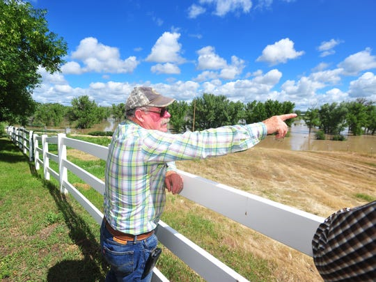 Norm Schertenleib points to different pastures on his property south of Vaughn now underwater due to Sun River flooding.