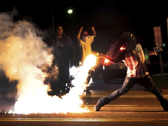 Edward Crawford Jr. throws a container of tear gas