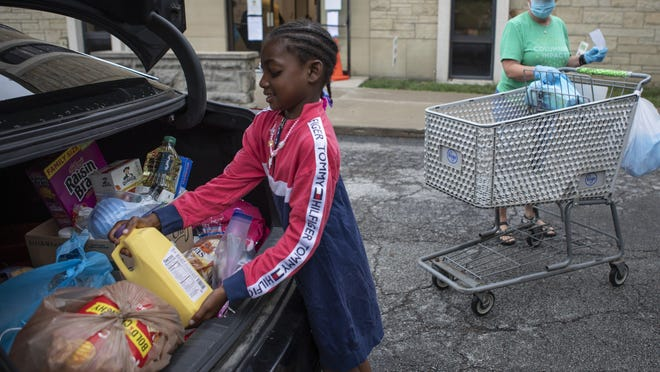 Malaysia Tucker, 7, helps her mom, Tiffany Miller, not pictured, and volunteer Ouida Wheeler load groceries Tuesday at the Broad Street Food Pantry, which is located inside the Broad Street Presbyterian Church in Columbus on Tuesday.