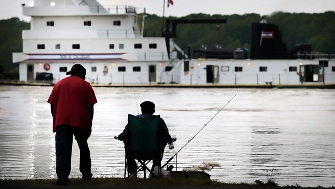 With the river at mid-level flood stage, Fishermen watch from Greenbelt Park as a barge chugs along south on the Mississippi River Wednesday morning at eye level with the bluff on the north side of Mud Island.