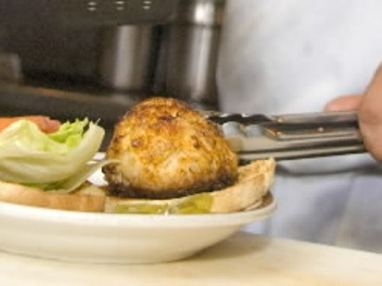A cook builds a crab cake sandwich during lunch time at the Reliance Café in West York.