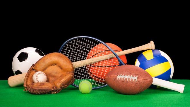 A collection of sports equipment suck as a football, basketball, baseball, tennin racquet, volleyball, soccer ball and catchers glove with a balck background.