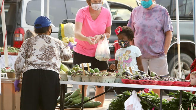 Kerri Hughes, left, Colette Magee, 5, and Linda Hughes shop for fresh produce, Saturday, Sept. 19, at the Downtown Farmers Market on Garrison Avenue.