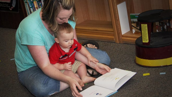 Brianne Thackeray, of Dallas, lets her son Bennett, 1 year, get a tactile introduction to books as story teller Brad Clark entertains on guitar.