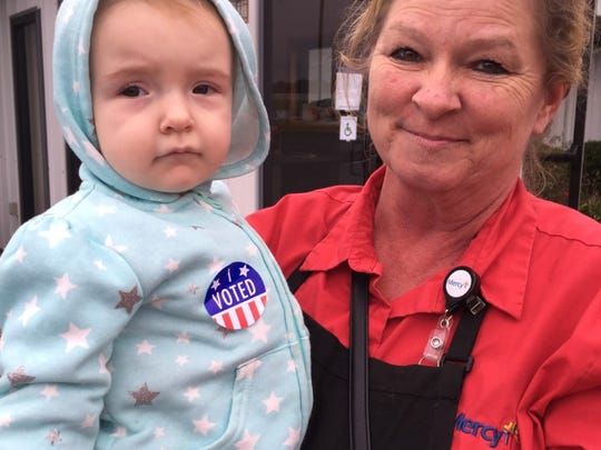 Teresa Goben cast her ballot for Donald Trump, while carrying granddaughter Aubree Johnson on her hip at a polling place north of Rogersville.