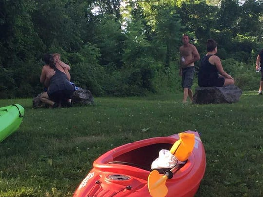 Kayakers console themselves on the banks of the Swatara Creek in Jonestown after one of their group may have drowned.