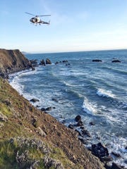 This photo provided by the California Highway Patrol shows a helicopter hovering over steep coastal cliffs Tuesday, March 27, 2018, near Mendocino, Calif., where a vehicle, visible at lower right, plunged about 100 feet off a cliff along Highway 1.