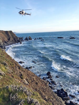 This photo provided by the California Highway Patrol shows a helicopter hovering over steep coastal cliffs Tuesday, March 27, 2018, near Mendocino, Calif., where a vehicle, visible at lower right, plunged about 100 feet off a cliff along Highway 1, killing all five passengers.