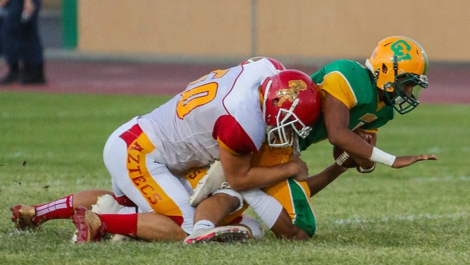 Palm Desert linebacker Jack Queenan tackles Coachella Valley quarterback Armando Deniz on Friday night.