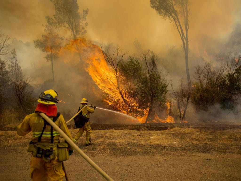 Firefighters douse a backfire while battling the Rocky Fire near Clearlake, Calif. The fire, one of dozens raging in drought-parched Northern California, has destroyed 24 residences and scorched 60,000 acres, according to CalFire.