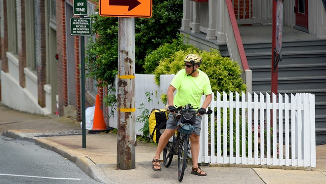 Bicyclist T.J. Forrester looks for cars as he prepares to turn onto South Lewis at Johnson Street while cycling in downtown Staunton on Tuesday, June 7, 2016. Currently visiting Staunton, Forrester resumes his 12,00 mile 2-year bicycling trek, which he is currently 1,600 miles into, next week when he sets out for Seattle.