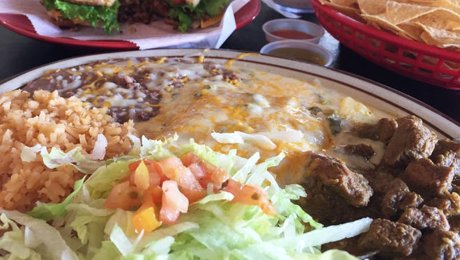 Combo plate #2 ($8) with two enchiladas, stuffed with cheese, a side of green chile con carne, with beans and rice.
